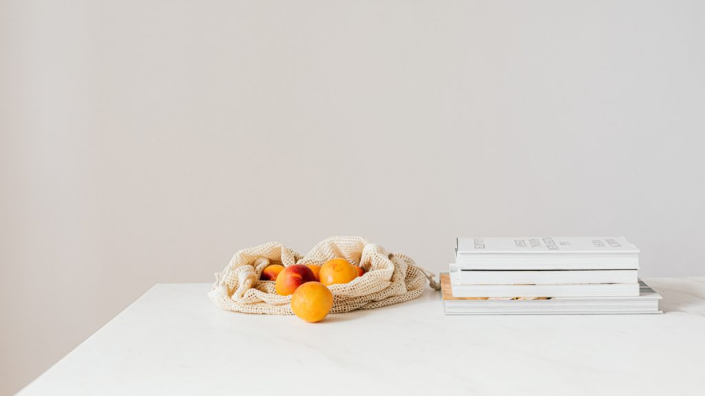 A photo of a basket of Apricots next to a stack of books on a table