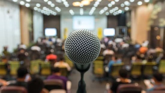 A photo of a microphone in front of a live audience