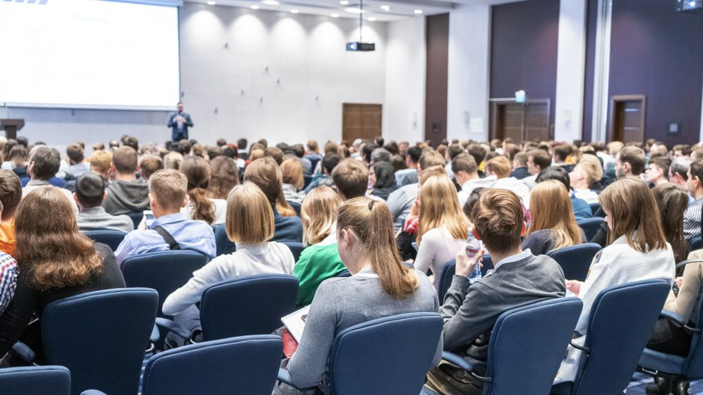 A photo of a seminar with a live speaker and an audience