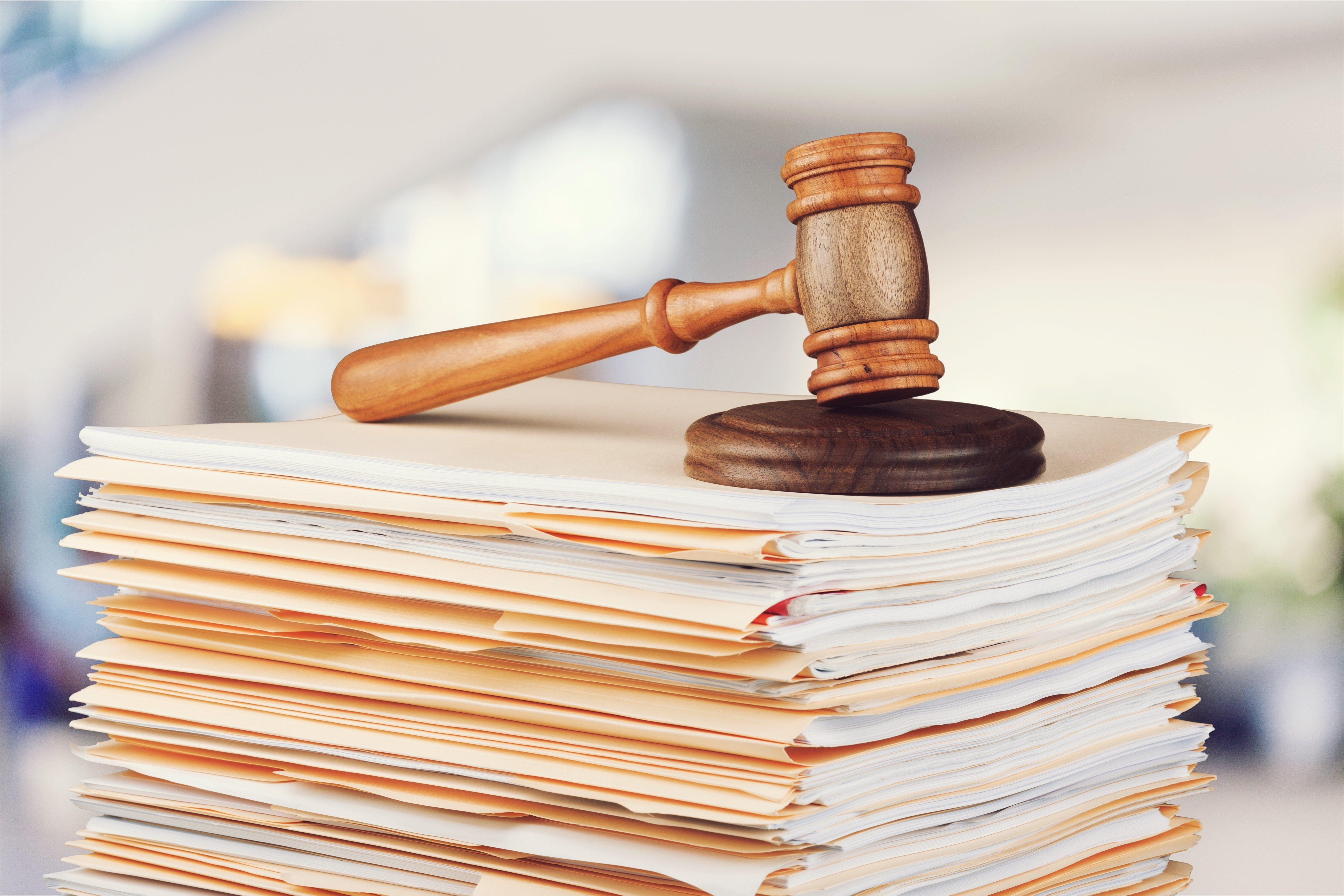 A photo of a stack of documents under a gavel.